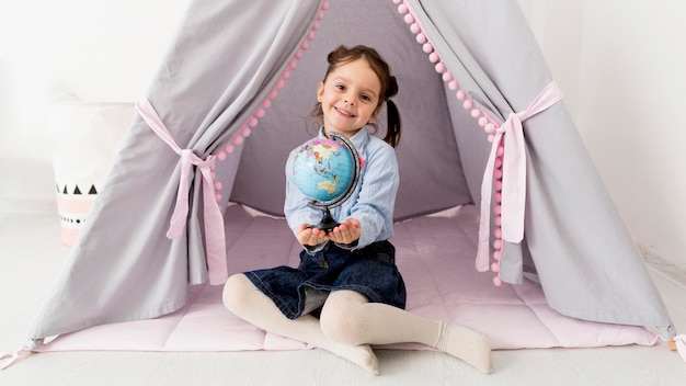 Молодая девушка с глобусом позирует в палатке