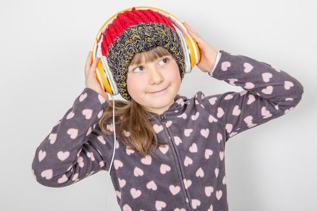 手袋と羊毛の帽子を持つ少女はヘッドフォンで音楽を聴いています