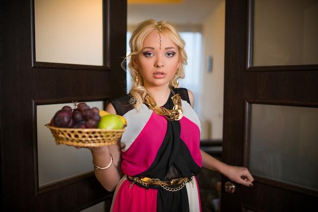 Молодая девушка с золотыми украшениями несет плетеную корзину с фруктами