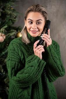 Ragazza giovane con maglione verde mantenendo una conversazione con il telefono cellulare