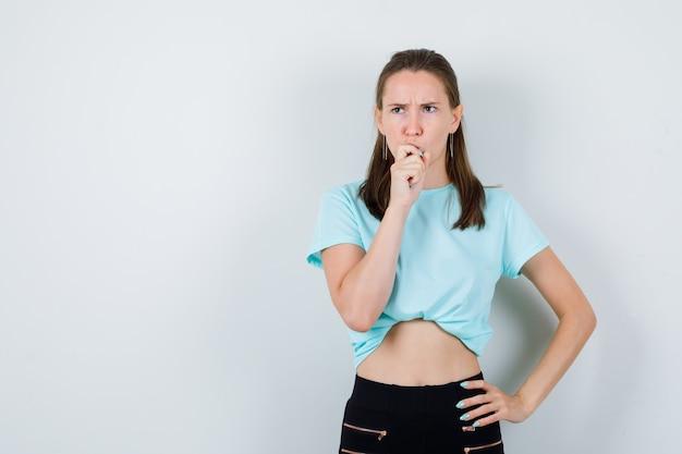 Молодая девушка с рукой на рту в бирюзовой футболке, штанах и озадаченный вид, вид спереди.