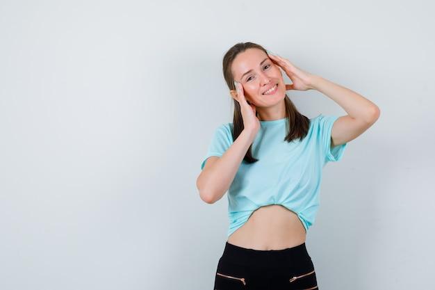 Giovane ragazza con le mani sul viso in t-shirt turchese, pantaloni e guardando felice, vista frontale.