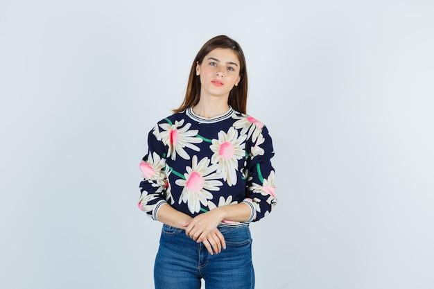 꽃무늬 스웨터, 청바지를 입고 귀엽고 앞모습을 보고 손을 앞에 두고 있는 어린 소녀.