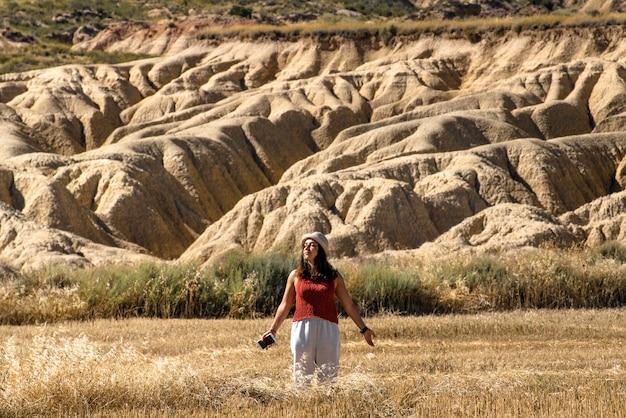 Молодая девушка в шляпе, коричневой рубашке и белых штанах, путешествующая по барденас-реалес-наварра