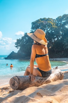A young girl with a hat sitting on a log on the beach of punta sal in tela
