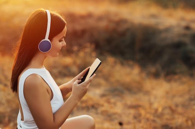 日没時に丘の上で彼女のスマートフォンから音楽を聞いているヘッドフォンを持つ少女。