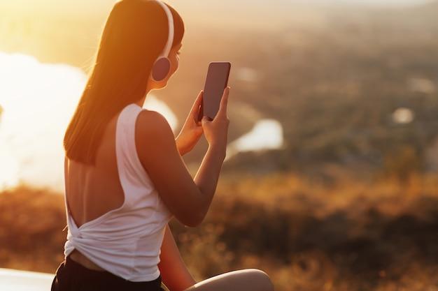 Молодая девушка с наушниками, слушая музыку со своего смартфона на холме во время заката.