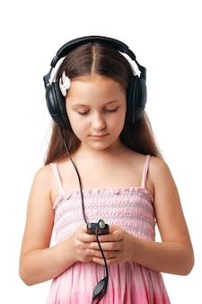 彼女の携帯電話やプレーヤーで何かを見ているヘッドフォンを持つ少女