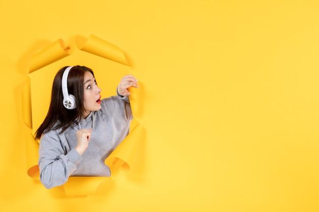 Молодая девушка с наушниками на желтой бумаге фон ультразвук музыка аудио звук