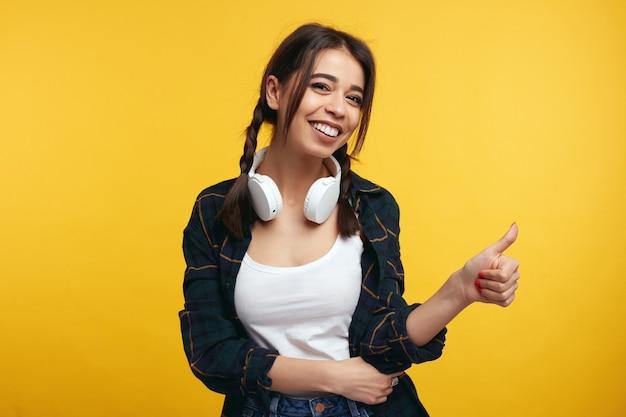 헤드폰을 가진 어린 소녀는 노란색 벽 위에 절연 제스처처럼 보여줍니다