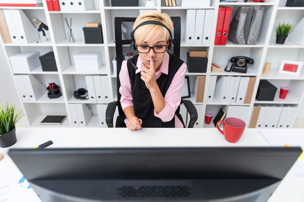 A young girl with headphones sitting at the computer table and raised her finger to her lips.