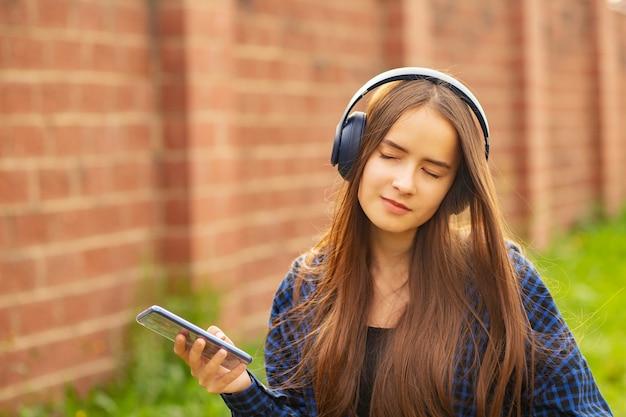 夏に街を歩き、音楽を聴き、楽しんで、笑顔でヘッドフォンを持った少女