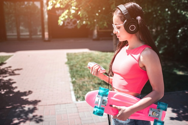 Young girl with headphones walking on the street
