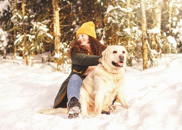 겨울 공원에서 그녀의 사랑하는 강아지 래브라도 어린 소녀