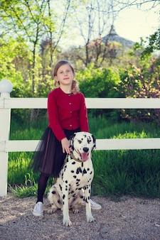 Молодая девушка со своими далматинскими собаками в весеннем парке.