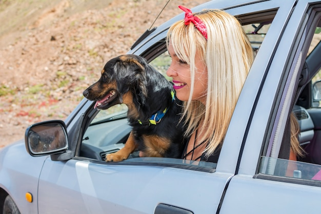 Young girl with her dog in the car traveling on summer vacation.