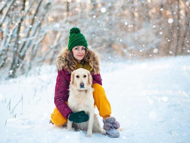 Молодая девушка с собакой обнимает белый золотистый ретривер
