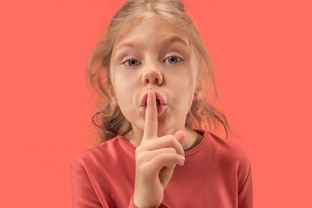 Молодая девушка с ее пальцем на ее рот на стене коралла