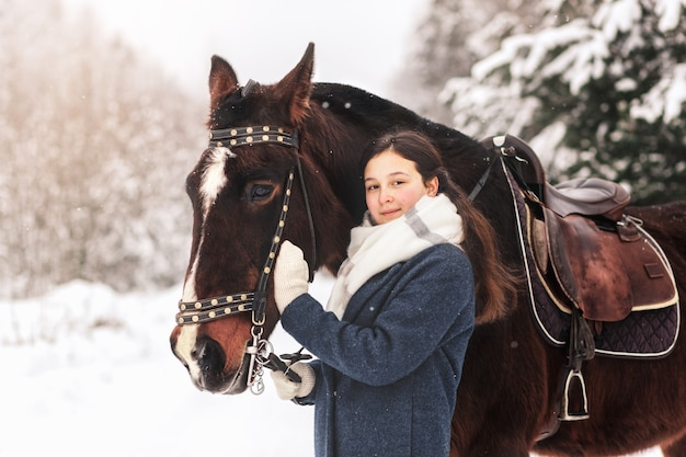A young girl with a horse in winter in the woods. communicating with nature and animals