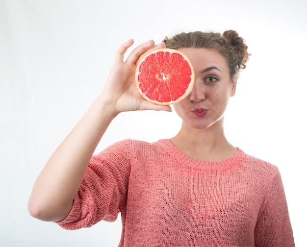 Молодая девушка с сочными и здоровыми грейпфрутами на белом фоне