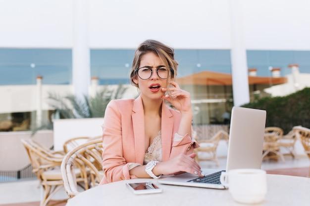 不機嫌そうな表情、イライラしたり不満そうな表情でストリートカフェでラップトップを持つ少女。スタイリッシュなピンクのジャケット、メガネ、白い時計を着ています。
