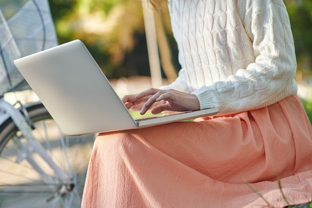 A young girl with a laptop sitting onthe bench in the park