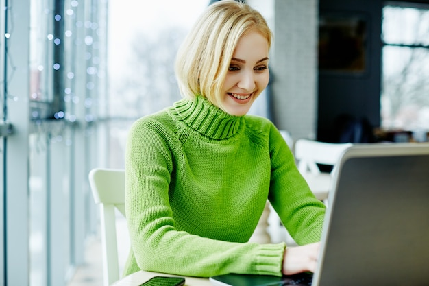 Young girl with light hair wearing green sweater sitting in cafe with laptop, portrait, freelance concept, online shopping.