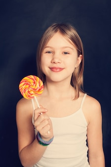 Young girl with lollipop on background
