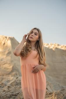 夏に長いブロンドの自然な髪の少女