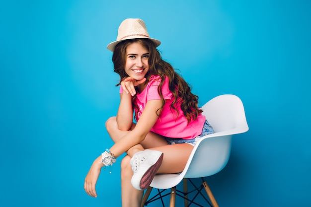 Young girl with long curly hair in hat is posing in chair on blue background in studio. she wears shorts, pink t-shirt, white sneakers. she keeps leg on knee and smiles to camera.