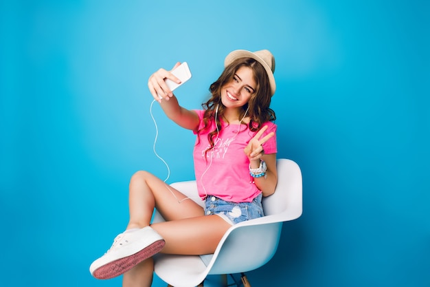 Young girl with long curly hair in hat listening to music with headphones in chair on blue background in studio. she wears shorts, pink t-shirt, white sneakers. she makes selfie-portrait.