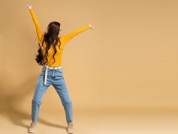 Молодая девушка с длинными вьющимися волосами в оранжевой толстовке танцует, подняв руки на пастельный апельсин.