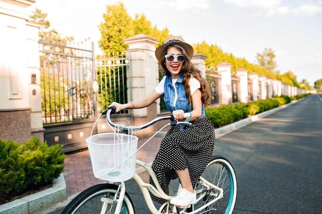 サングラスで長い巻き毛を持つ少女は、道路で自転車を運転して楽しいです。彼女はロングスカート、ジャーキン、帽子をかぶっている。彼女は笑顔で楽しそうです。