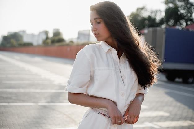 흰 셔츠를 입은 긴 검은 머리를 가진 어린 소녀가 밝은 햇살 아래 거리에 서 있습니다.