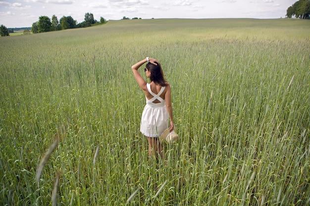 Молодая девушка с длинными темными волосами, идет по зеленому полю с высокой травой лицом к камере в коротком белом платье и соломенной шляпе