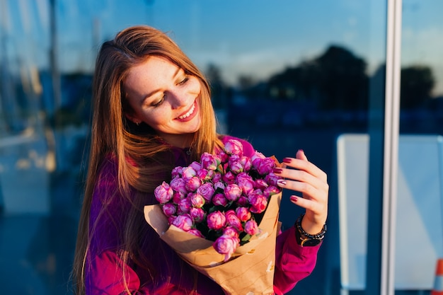 Young girl with long hair posing with flowers on blue background on fresh air