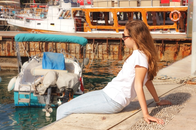 Young girl with long hair sits on the pier in the yacht port and looks at the blue sea