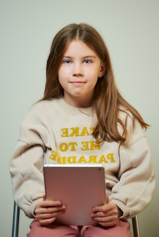 A young girl with long hair studying with a tablet. a happy child with a smile holds a tablet computer.