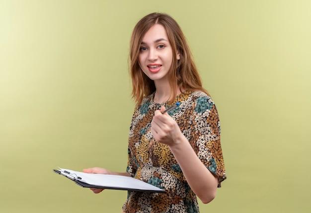Giovane ragazza con i capelli lunghi che indossa abiti colorati tenendo appunti che punta con la penna alla fotocamera a sorridere