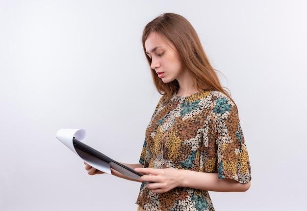 Giovane ragazza con i capelli lunghi che indossa abiti colorati tenendo appunti con pagine vuote guardandolo con faccia seria