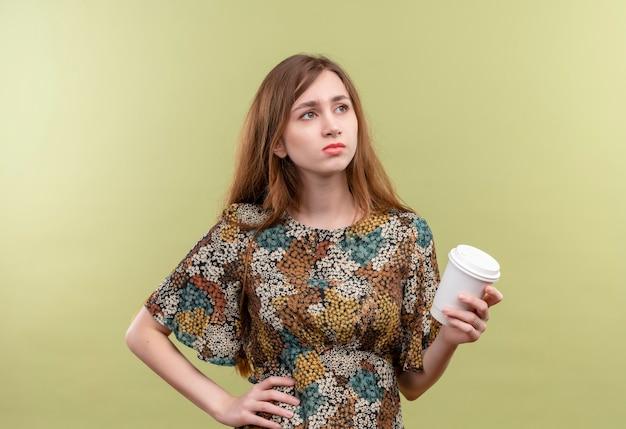 Giovane ragazza con i capelli lunghi che indossa abiti colorati tenendo la tazza di caffè guardando da parte scontento