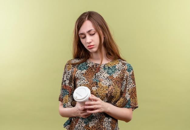 Giovane ragazza con i capelli lunghi che indossa abiti colorati tenendo la tazza di caffè guardandolo con espressione triste sul viso