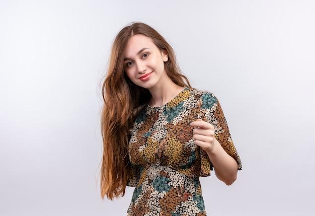 ポジティブで幸せな笑顔のカメラを見てカラフルなドレスを着て長い髪の少女