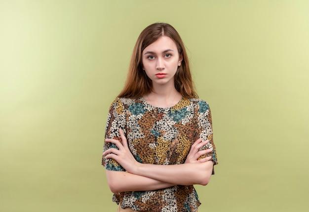 Giovane ragazza con i capelli lunghi che indossa abiti colorati guardando la telecamera scontento con le braccia incrociate sul petto