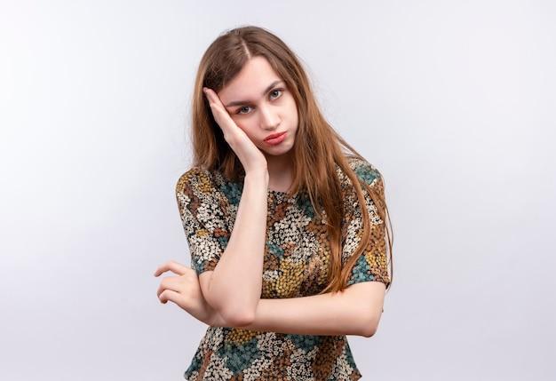 Giovane ragazza con i capelli lunghi che indossa abiti colorati guardando la telecamera appoggiando la testa a portata di mano stanchi e annoiati