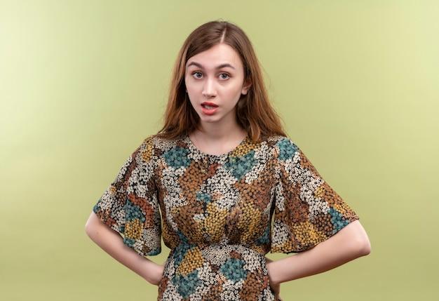 Giovane ragazza con i capelli lunghi che indossa abiti colorati che guarda l'obbiettivo con la faccia arrabbiata