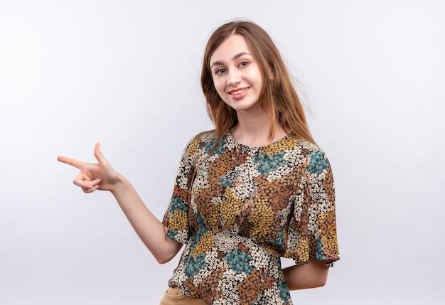 Молодая девушка с длинными волосами в ярком платье выглядит уверенно, указывая указательным пальцем в сторону, улыбаясь