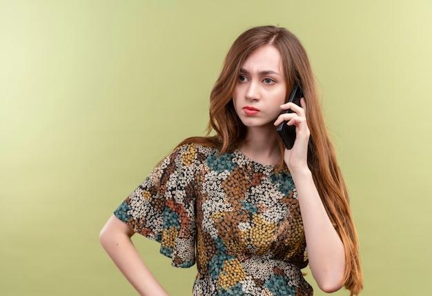 携帯電話で話している間混乱しているように見えるカラフルなドレスを着ている長い髪の少女