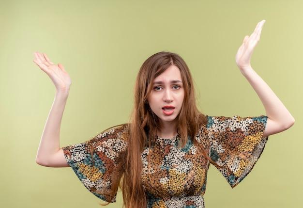 Giovane ragazza con i capelli lunghi che indossa abiti colorati cercando incerti e confusi alzando le mani, non avendo risposta