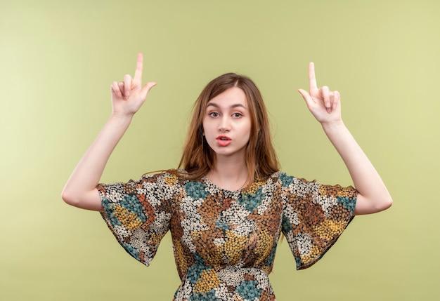 Giovane ragazza con i capelli lunghi che indossa abiti colorati che punta il dito indice verso l'alto con seria espressione fiduciosa sul viso